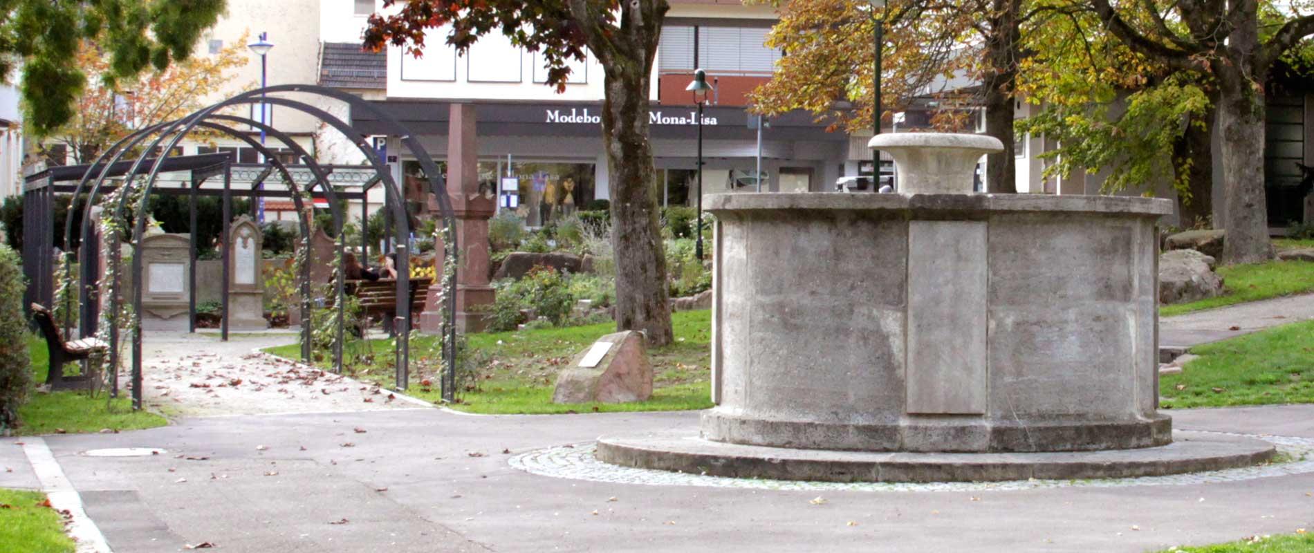 Kulturprojekt Schillerpark: Grabsteine im Hintergrund, im Vordergrund Sutor-Brunnen.
